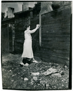 Mrs. Bella Iveson repairs fence of home at 111 Washington Ave.